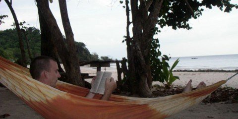 Charles Kosman reading a book in a hammock by the ocean