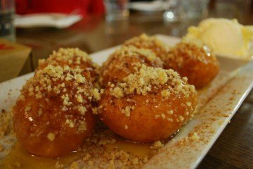 Loukoumades drizzled with nuts and honey