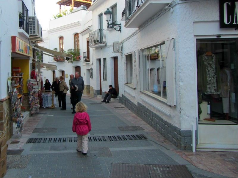 Little girl walking through the white village of Nerja