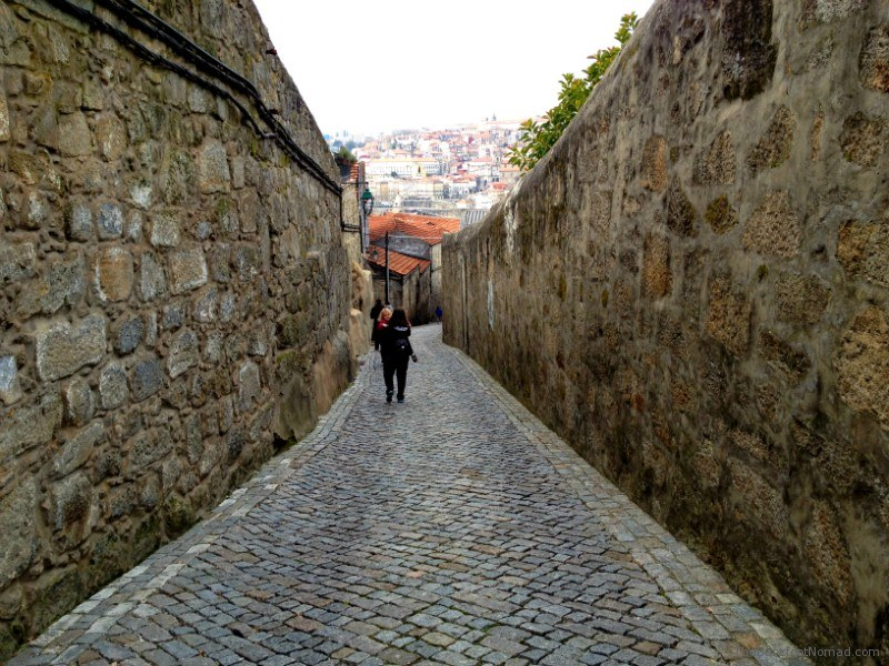 Mom carrying child through the Cobblestone Streets Porto Portugal