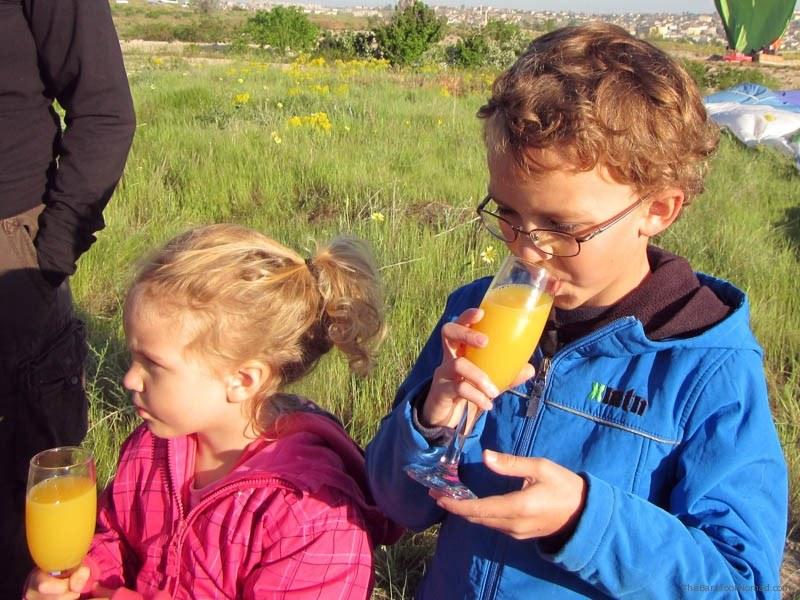 Kids celebrating with a glass of oj