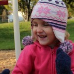 Little girl in touque smiling in fall
