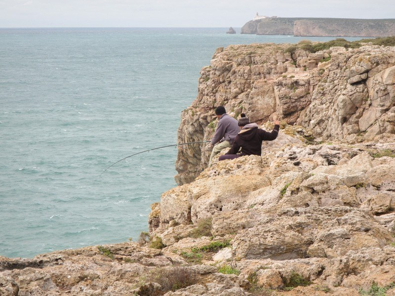 Fishermen standing precariously on the cliffs at Sagres Point