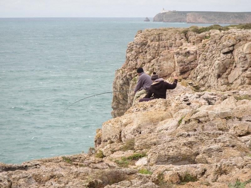 Fishermen straddling the cliffside bringing in their meal