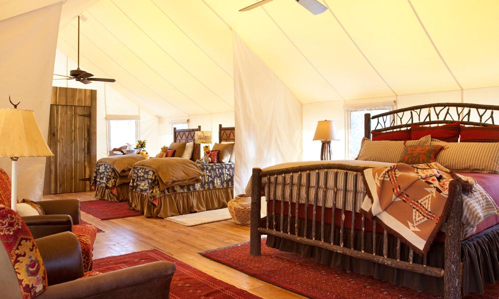 Plush bedding in a huge canvas tent while glamping at the Rock at Ranch Creek in Montana