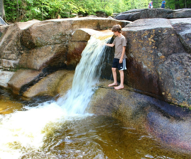 New Hampshire boy playing in the waterfall at Dianas Baths