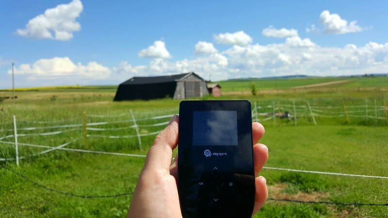 Tep Wireless working on a farm with barn in background