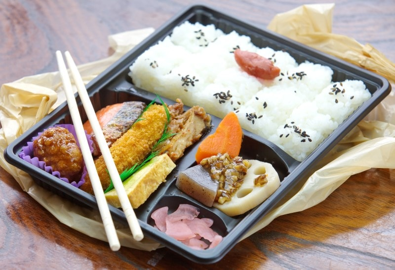 Japan Ekiben Bento box full of rice, meats and wooden chopsticks