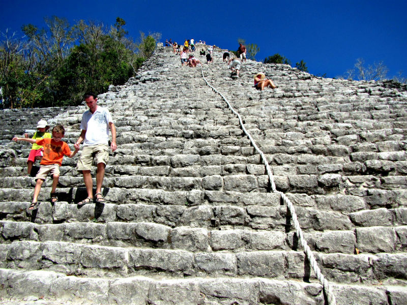 Dad and son descending the pyramid at Coba Mexico