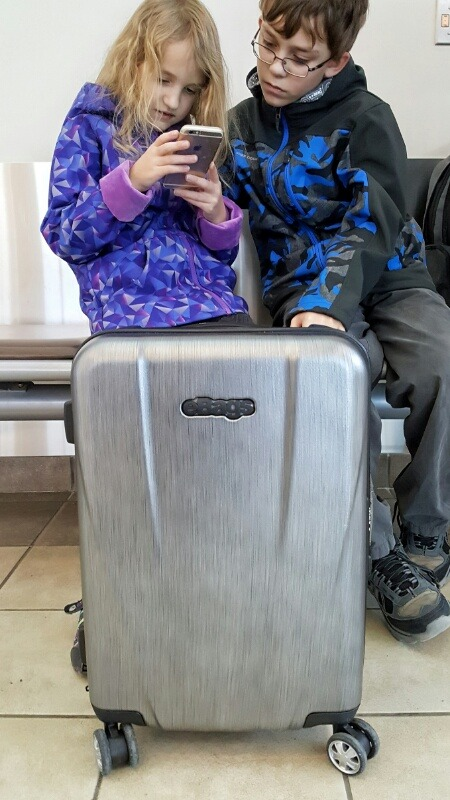eBags Allura 22 hardside carry-on with brushed steel look and our kids at the airport