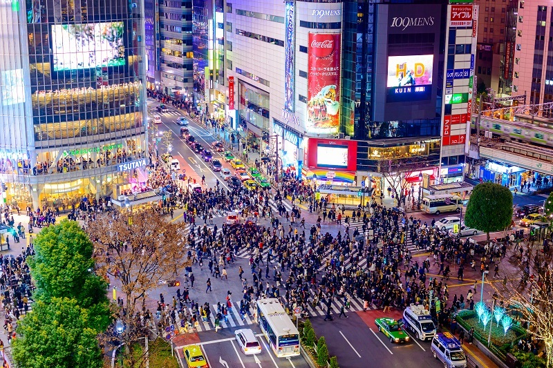 Pedestrians cross at Shibuya Crossing. It is one of the world's most famous scramble crosswalks in one of Toyko's most interesting neighbourhoods.