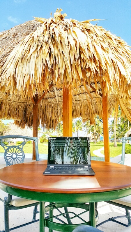 Laptop under a thatched umbrella at Victoria House Belize