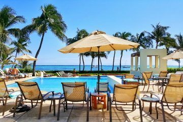 Poolside loungers with view of the ocean The Phoenix Belize Resort