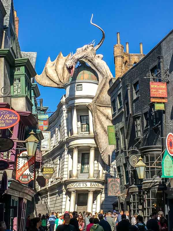 The Wizarding World of Harry Potter street with Gringotts Bank and Dragon