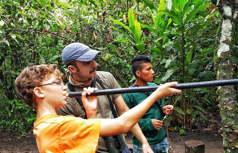 Boy learning to shoot a blow dart in the Ecuadorian Amazon