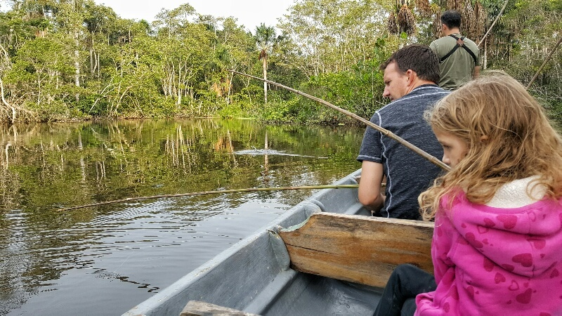 Dad and daughter fishing for piranha in the Amazon