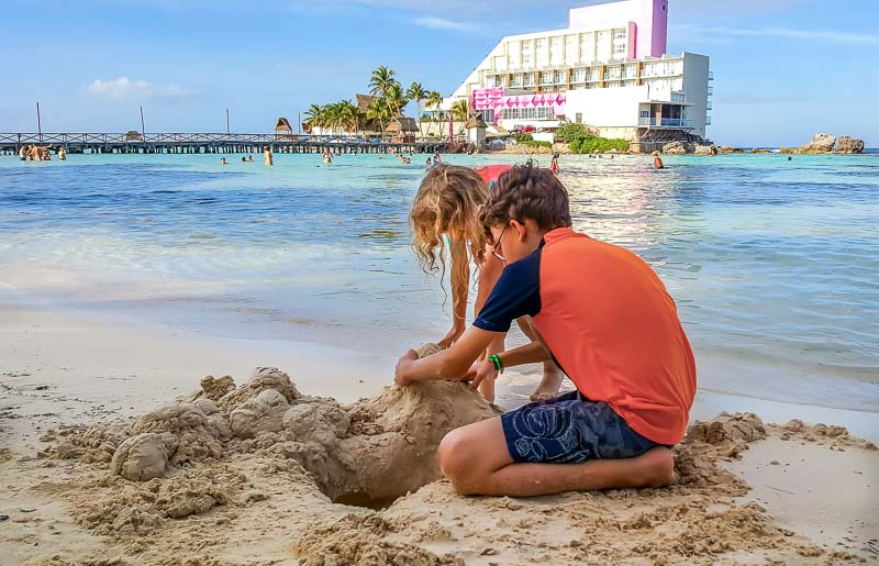 kids playing in the sand in Isla Mujeres Mexico