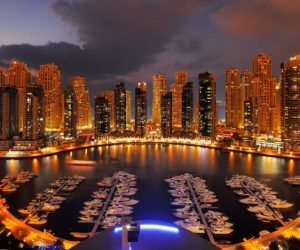 Dubai Marina at night with lighted walkways and anchored boats