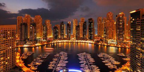 Dubai Marina at night with lighted walkways and anchored boats