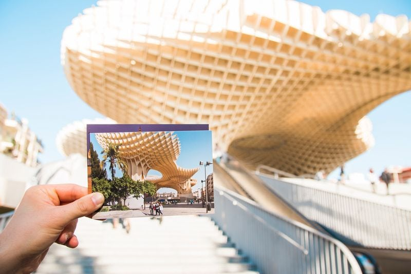 photo held up in front of tourist landmark for ways to preserve your travel memories