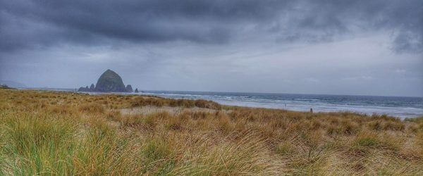Canon beach Oregon clouds and field in front