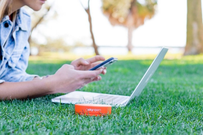skyroam solis portable wifi with laptop in the grass