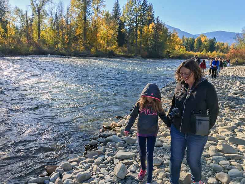 mom and daughter walking along Adams River riverbank in British Columbia during the Sockeye salmon run