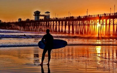 Silhouetted surfer at sunset in Oceanside California on a great weekend getaway from Los Angeles