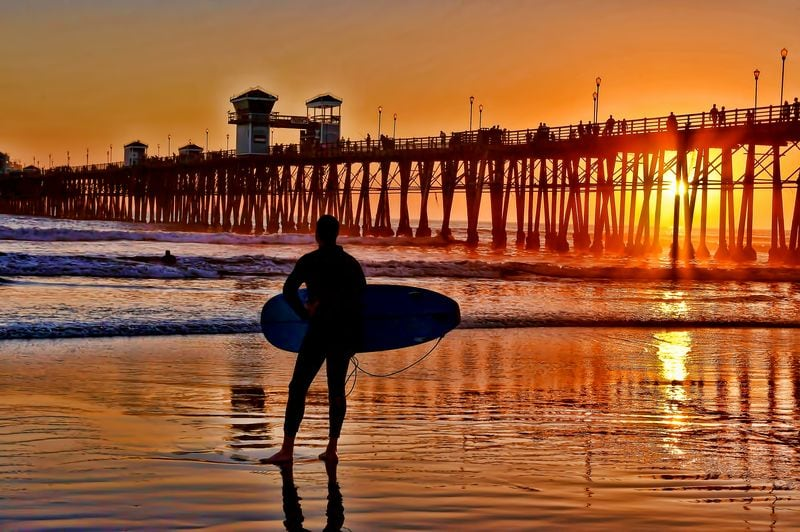 Silhouetted surfer at sunset in Oceanside California weekend getaway from Los Angeles