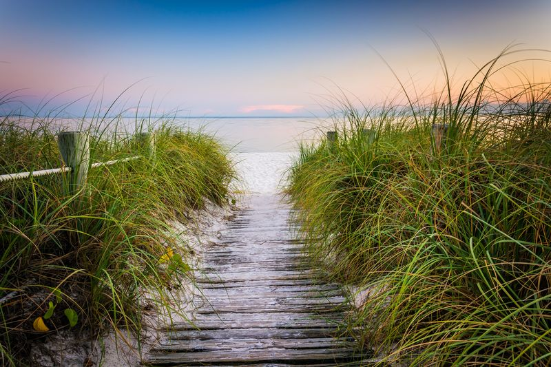 Smathers Beach at sunset with grasses and fence along wooden path One of the Best Beaches in the Florida Keys