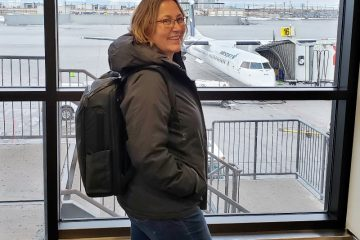 Nomatic backpack side view on woman at airport
