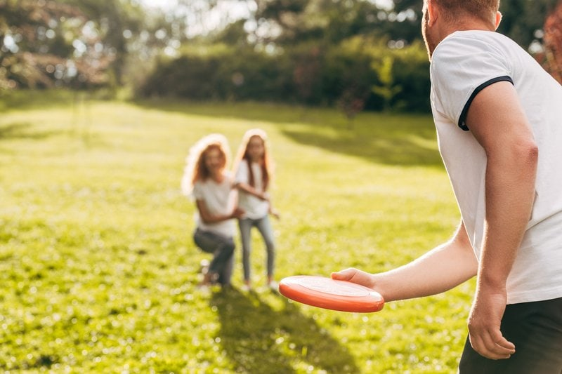 dad throwing Frisbee to mom and daughter in back yard