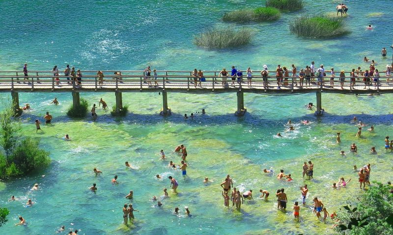 People swimming by a wooden bridge Krka National Park Croatia