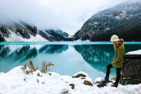 best travel vloggers on Youtube woman in front of Canadian lake in winter